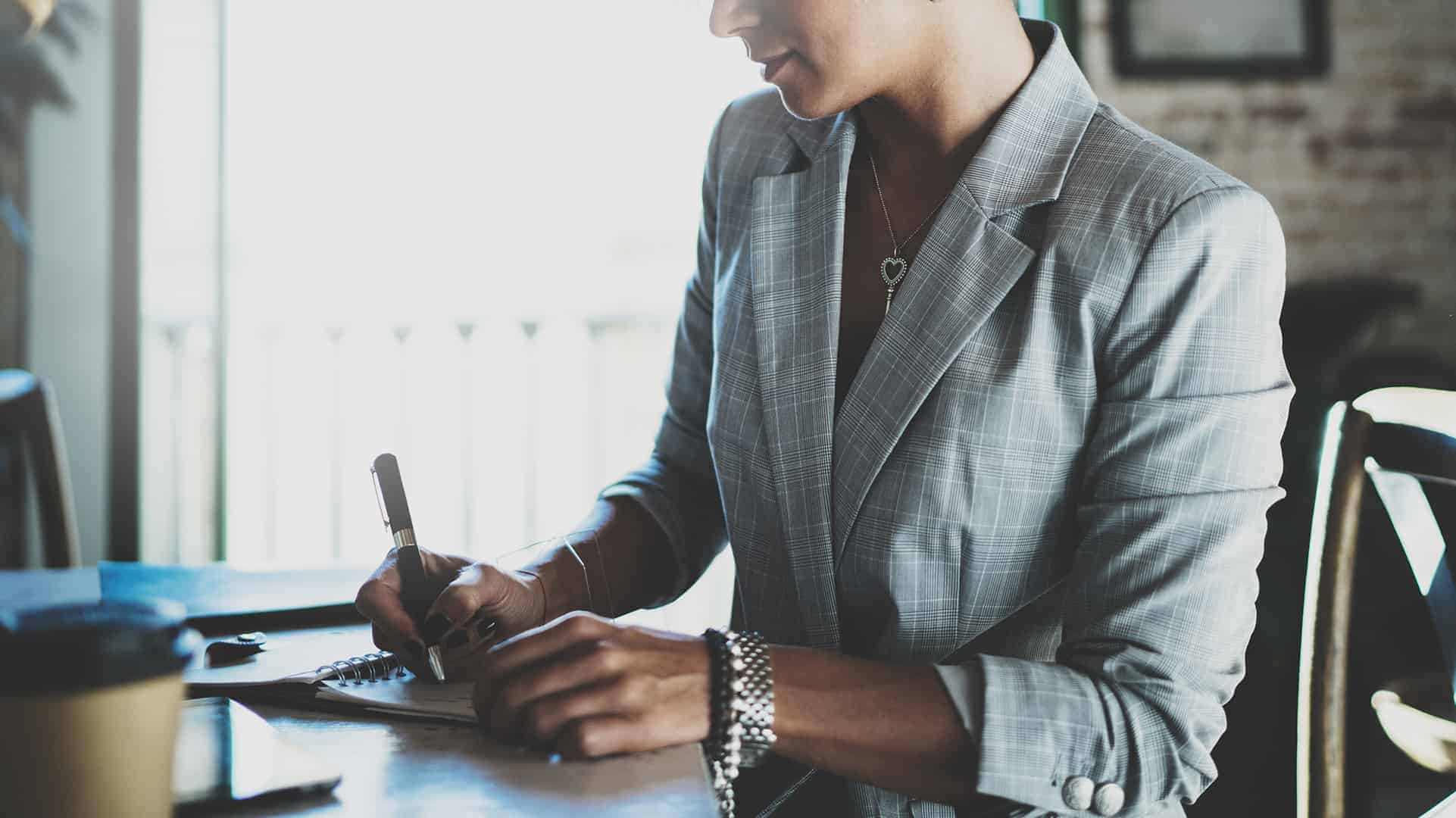 Image of young businesswoman writing something in note pad while sitting