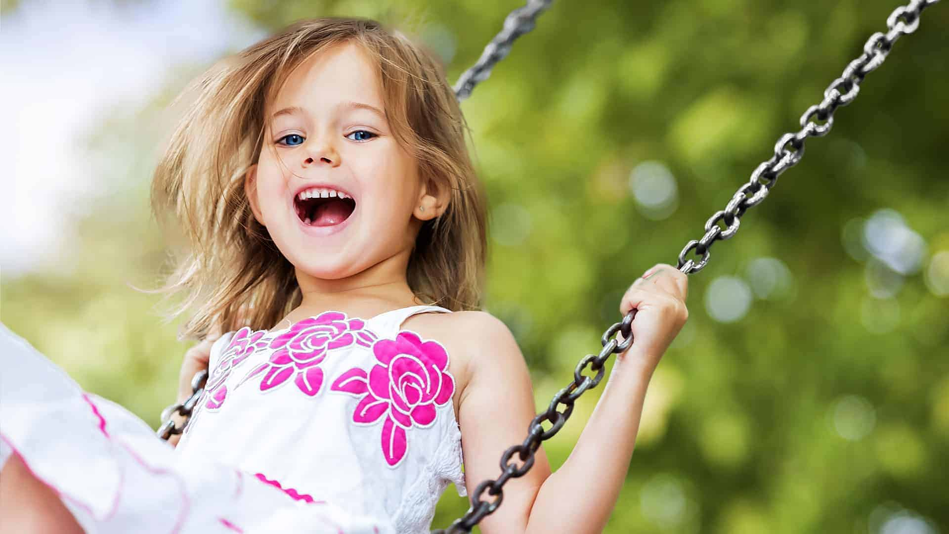 image of happy young girl on a swing