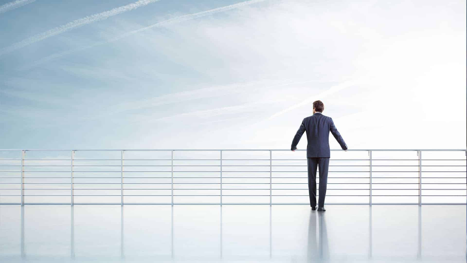 Businessman standing on a roof and looking sky
