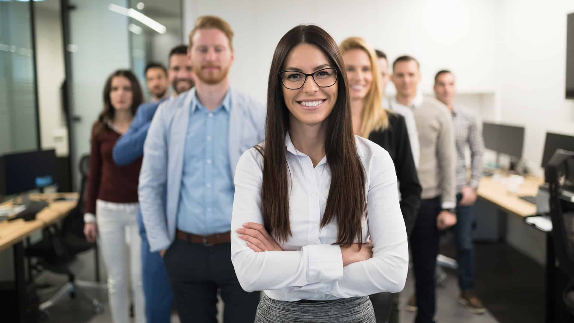 business team posing in an office with a female in the front