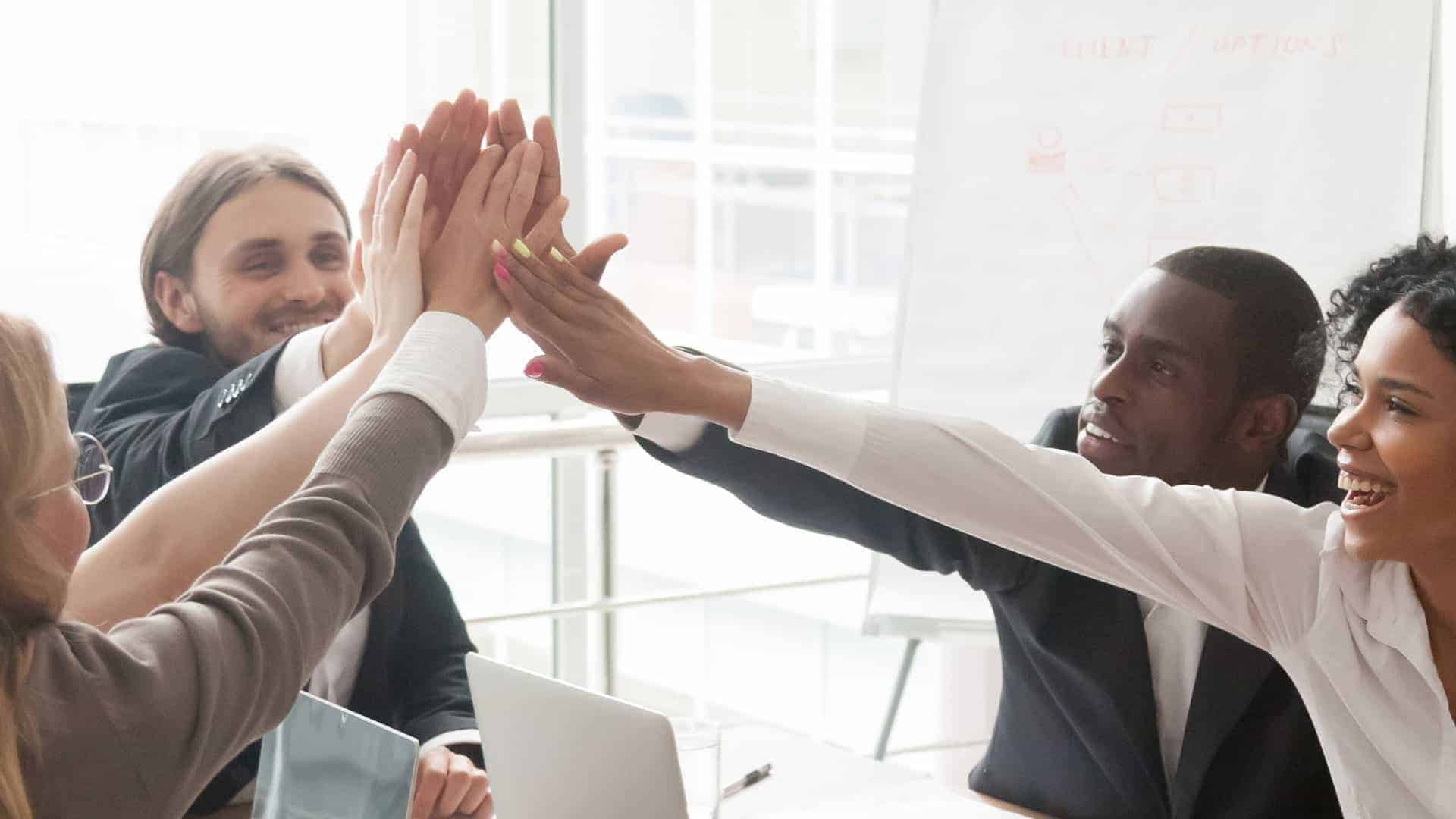Image of business people giving a group high five