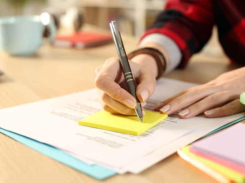 Women writing on a yellow sticky note with a cup in the back which is blurred